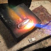 Material auf Kohle schmelzen.