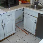Schimmelpilze an einer Wand in einem gering belüfteten Hohlraum hinter Küchenmöbeln