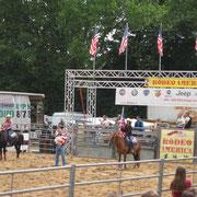 Das Rodeo beginnt! Wagemutige Männer und Frauen auf ihren Pferden und Bullen...
