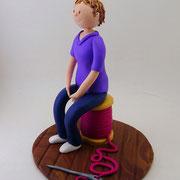 Tortenfigur Frau sitzend auf Garnrolle
