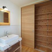 脱衣室は広く、タイルの洗面台に収納スペースを設けています。
