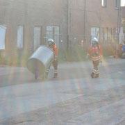 Ein Servicetrupp bringt unter PA die Behälter zu Lagerung des Gefahrgutes an die Unfallstelle