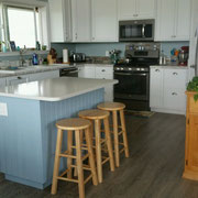 Coastal kitchen with clean white cabinets and soothing blue island.