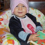 16. Monat - ich habe mir die Mütze meiner Schwester selbst aufgesetzt...