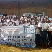 """A. Siirewabo et toutes les étudiantes présentent la belle banderole du projet """"Eau et serviettes""""."""