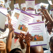 "The children are receiving the booklet om mensturation;  ""La puberté et l'hygiène menstruelle""."