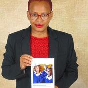 "Rita Marque Mbata, President Women's Comfort Corner Zimbabwe with booklet ""Entering Womanhodd"""