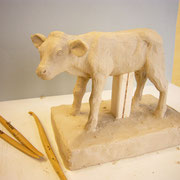 Mit Hilfe eines Stützgerüsts aus Holz und Draht wird ein Kälbchen modelliert.