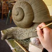 Zuerst wird die Schnecke direkt auf dem Stein in Ton modelliert.