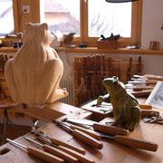 Mit Meissel, Hammer und Keramik-Modell wird das Lindenholz weiter bearbeitet.