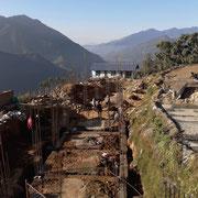 An den Fundamenten sind die beiden Schulgebäude bereits ablesbar. Nach 5 Pfeilerpaaren kommt das Treppenhaus zwischen den Gebäuden.