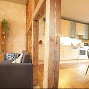Die originale Holzbalkenwand trennt den Küchenbereich optisch vom Wohnbereich