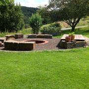 Feuerstelle aus Ziegelstein (trocken verlegt) mit Grauwacke Sitzsteinen und Holzauflage als Sonnenliege