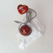 Rode Jaspis met rvs asbuisje op ruwe marmer.