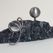 Bergkristal met rvs asbol op ruwe graniet.