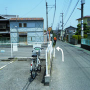 村田医院さんを通過後20メートル程で左手に大きな駐車場。入口左折。