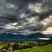 Sonnenstrahlen brechen die dunklen Regenwolken über Oberstdorf
