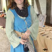 Sylvie démontre la fabrication d'une ceinture en laine.