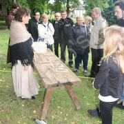 Cécile invite les curieux à graver les chiffres romains sur des tablettes de cire.