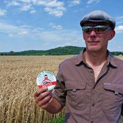 Michael Seroka mit der Hutzel-Plakette vor einem Weizenfeld im Weserbergland. Passt ;-)