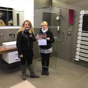 Unsere Mitarbeiterin Jeannine Heinze freut sich mit Frau Galina Wonnenberg über den gewonnen Weihnachtsbaum- Gutschein aus dem Gewinnspiel #3