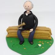 Tortenfigur sitzend auf Holzstapel