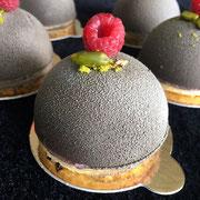 Schoggikuppel gefüllt mit Beeren-/Pistazienmousse auf Biskuit