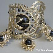 П-1218. Cuff- браслет ручной работы. Ювелирный сплав с позолотой, 3 подвижных чарма, браслет легко регулируется по запястью.