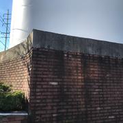 『トラスト・ミー』のオイルタンク。マリアが上った壁のコンクリートはレンガで補装され、黄色の花が咲いていた花壇は、今では茂みになっていた。