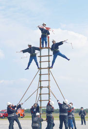 はしご乗りでポーズを決めた消防団員=11日、市消防本部