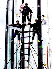 はしご乗りで、トリを務めた女性団員3人が「火の用心」などの垂れ幕を披露した=12日、市中央運動公園