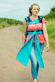 Huckepack Wrap Tai, Babytrage mit auffächerbaren Schulterträgern, ergonomisch geformter Hüftgurt mit Schnalle, stufenlos verkleinerbares Panel.