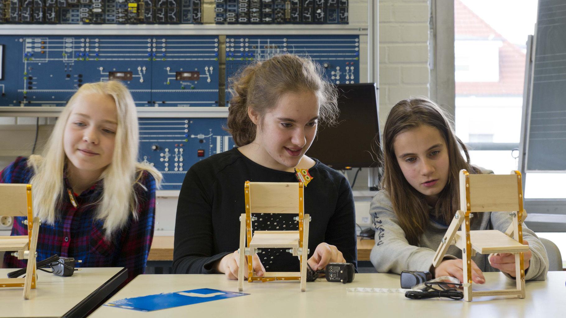 """Drei """"Girls"""" beim konstruieren einer Ladestation für das Handy"""