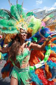 Brasilianische Tänzerin beim Karneval der Kulturen Berlin mit üppigem Federschmuck. Foto: Helga Karl