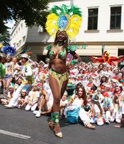 Vorführung einer wenig bekleideten Tänzern einer brasilianischen Gruppe, die anderen sitzen am Boden.Aufstellplatz Karneval der Kulturen. Foto: Helga Karl