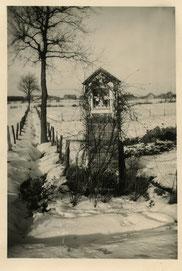 Oude foto zwart-wit. Een kapel aan een ondergesneeuwd weiland.