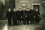 Oude foto zwart-wit. zeven jongens met winterjas voor een boerderij.