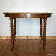 Ovaler Tisch, um 1900, Nussbaum, gedrechselte Beine, Messingräder, € 400,00