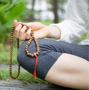 Mit Gebetskette meditieren, beten, Mantras rezitieren, im Wald, Frau in der Meditation