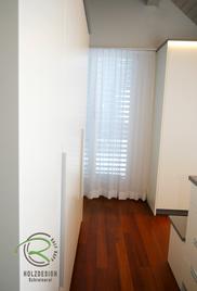 Ankleidezimmer mit einem weißen Kleiderschrank mit Aluminium-Griffleiste