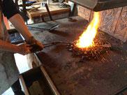 Schmied an der Esse erwärmt Stahl