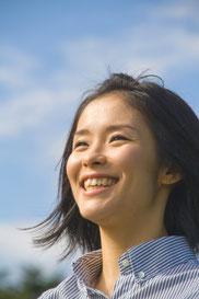空をバックに笑顔の女性
