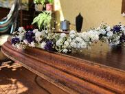 Geflecht aus weißen und violetten Blumen liegt auf einem antiken Tisch aus Holz.