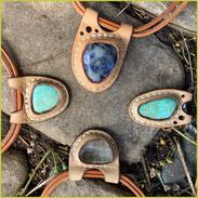 Vier Halsketten mit in pflanzlich gegerbtes Leder  eingefassten Halbedelsteinen.