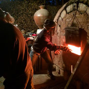 Photo of me stoking the front of a wood kiln, taken by Matt Hepler.