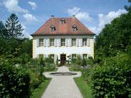 """Das  Wohnhaus am Rande der Eremitage erhielt Wilhelmine 1732 zum Geschenk. Als sie es erstmals sah, soll sie gesagt haben: """"Ah, ca serait mon plaisir"""" (Ah, das würde mir gefallen). Seither heißt das Gebäude Monplaisir."""