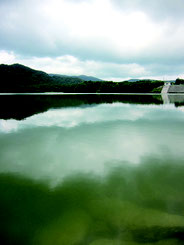 貯水量が横ばいとなっている真栄里ダム。上空に雲が垂れ込め、まとまった雨が降った=4日午後、於茂登岳近くの真栄里ダム