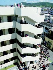 階段を上る新川小学校の児童ら=23日午前、石垣海上保安部新栄町宿舎