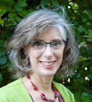 Joke Zonneveld heeft een vol kapsel van licht grijzend haar en een stralende glimlach, Ze draagt een bril, haar vest is lime groen. De achtergrond is een donkergroene beukenheg.