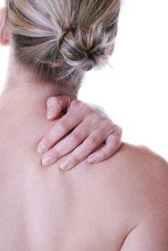 Frau fasst sich an verspannte Schulter. Nackenverspannung, Schlafprobleme, Schulterverspannung, Hirsekissen, Hirsespelzkissen